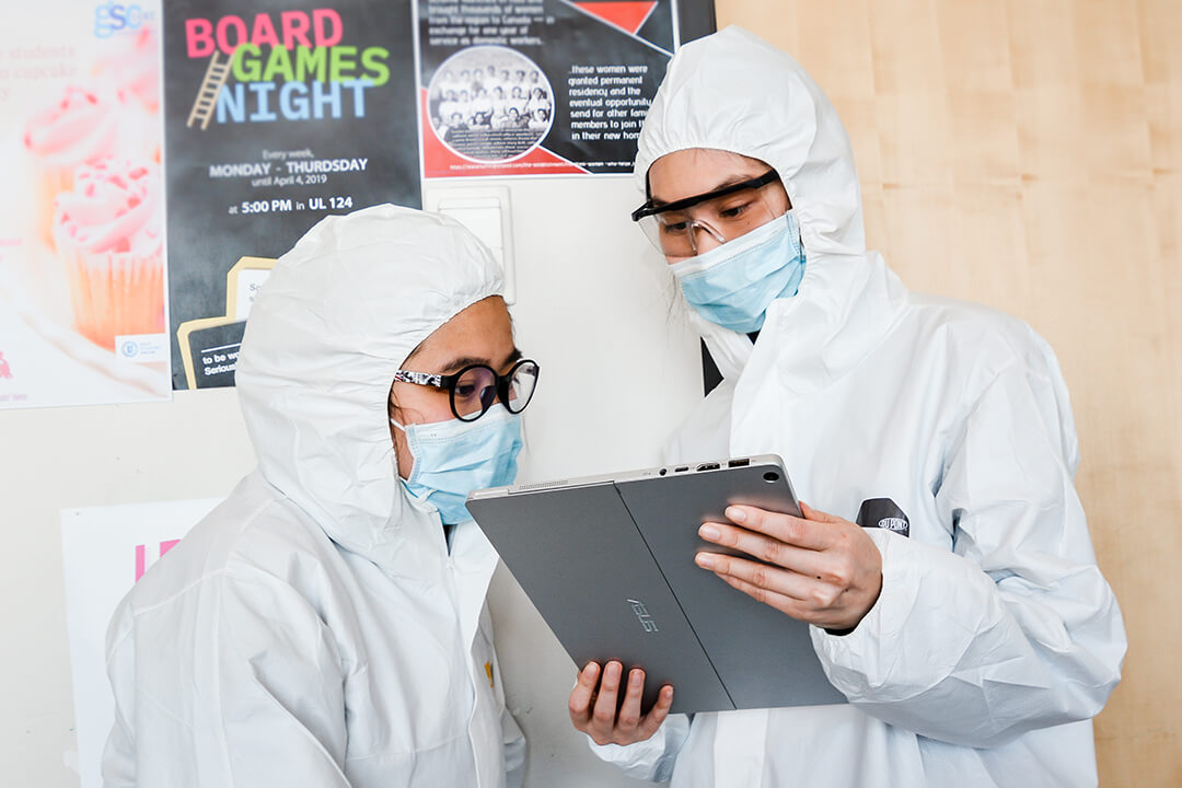 two girls with lab gear on looking at clipboard