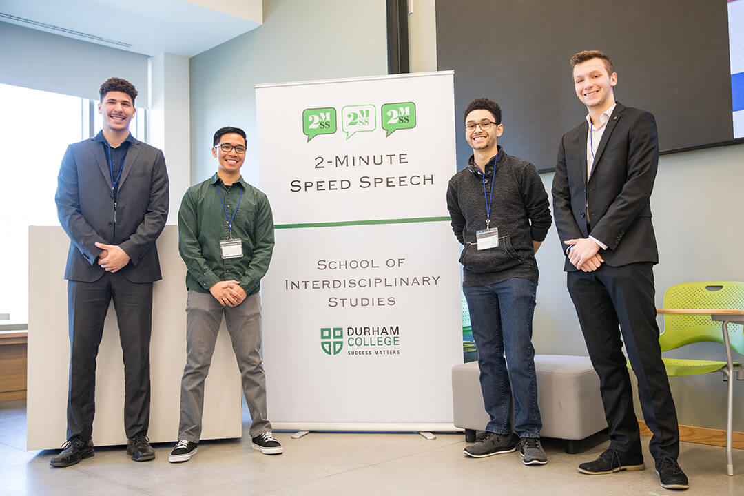 four guys standing and smiling by sign that says 2-minute speed speech