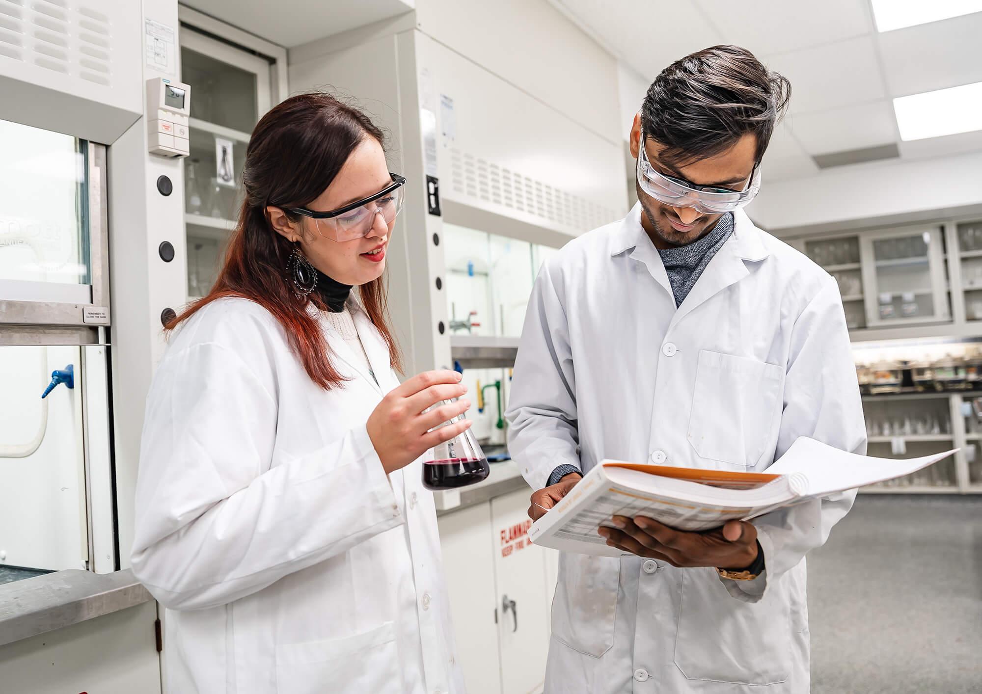 two laboratory technicians analyzing paperwork